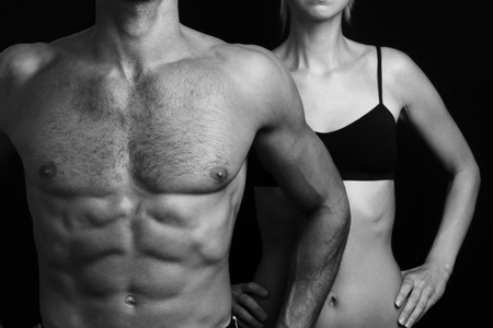 Bodybuilding, sport, fitness ,workout concept. Fit couple,  strong muscular man and slim woman posing on a black background Stock Photo