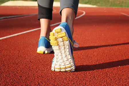 sport shoe: Athlete runner feet on stadium track. Closeup on female shoe and legs. Woman autumn  fitness workout. Jogging, sport, healthy active lifestyle concept.