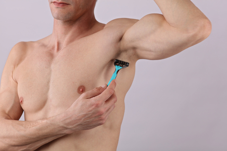Male body hair removal. Attractive muscular man using razor to remove hair from his armpit
