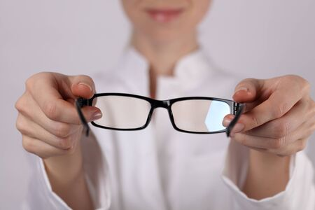 doctor giving glass: Eye care concept. Doctor ophthalmologist doctor ophthalmologist giving glasses to patient close up. Stock Photo