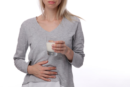 Dairy Intolerant person.Woman with stomach pain holding a glass of milk. Lactose intolerance, health care concept.