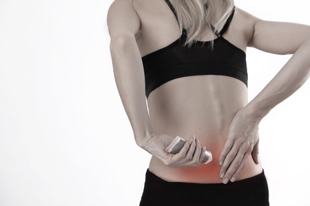 Woman suffering from back pain applying pain relief cream . Sports exercising injury.
