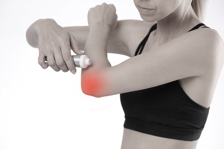 Woman suffering from elbow pain applying pain relief cream Stok Fotoğraf
