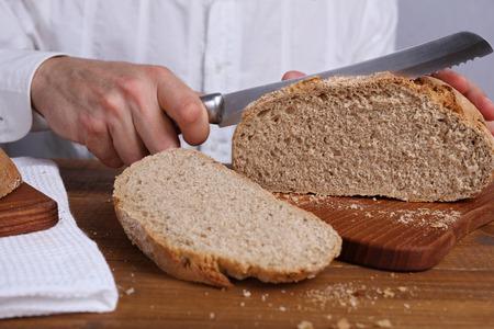 haciendo pan: Hombre corte sabroso pan de grano entero fresco. Concepto de alimentación saludable Foto de archivo