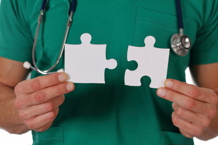 Doctor holding two pieces of a blank puzzle isolated on white background.