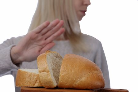 coeliac: Gluten intolerance and diet concept. Woman refuses to eat white bread. Selective focus on bread