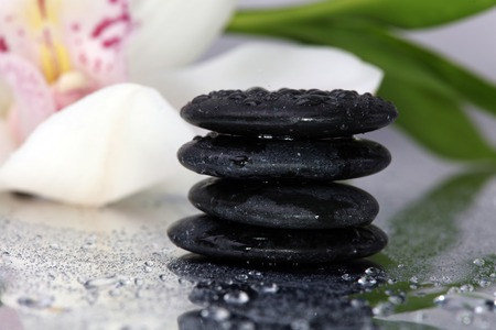 Spa background. Volcanic rock, bamboo and orchids on reflective background with raindrops. Relaxation, body care treatment, spa, wellness concept