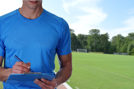 Football, soccer trainer with workout plan close up on football field background. Team sport, fitness and healthy life style concept.