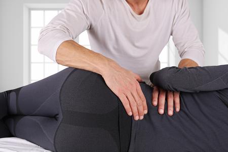 Vrouw die chiropraktijk achteraanpassing dicht omhoog heeft. Osteopathie, alternatieve geneeskunde, pijnverlichting concept