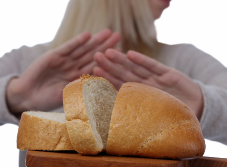 Gluten intolerance and diet concept. Woman refuses to eat white bread. Selective focus on bread
