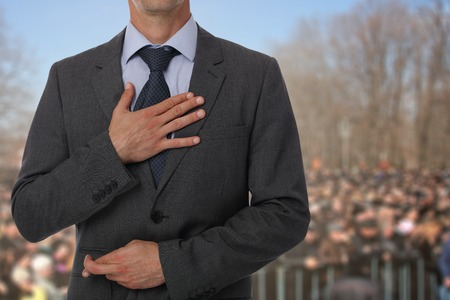Politician liar gives people impossible promises with fingers crossed on his back.