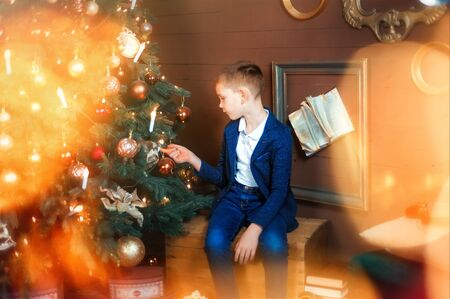 6 years old boy sit and look at beautiful christmas tree. Christmas lights around. Christmas eves and gifts. Child wait for presents in new year. Serious sad kid
