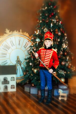 6 years old boy wearing like hussar with saber stay near christmas tree. Big clock and dollhouse on floor. Child in masquerade carnival costume of nutcracker. Dreams come true in christmas time