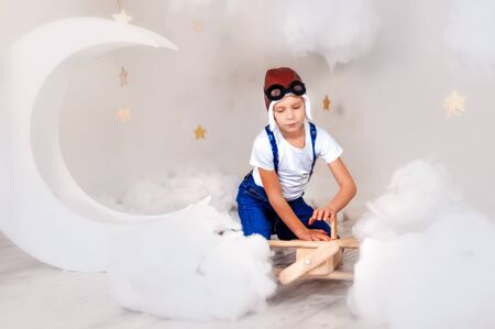 6 years old boy in airplane helmet, white t-shirt, blue jeans and suspender repair wooden airplane with clouds, stars and moon around. Happy childhood, dream about sky and travel. Travelling child