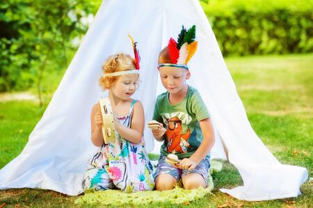 3 years old girl and 5 years old boy with feathers on head sit near white tent with tambourine and maracas in hands. Children pretend to be indian. Indians game in summertime. Children play music.