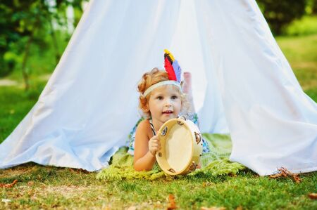 3 years old girl lay on ground near white tent with tambourine in hands and feathers on head. Child pretend to be indian. Indians game outdoors in summertime. Ecological lifestyle for children.