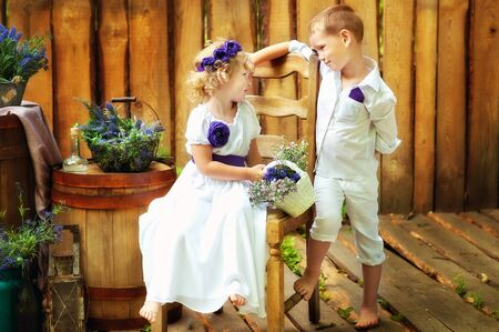 Small boy and girl in white clothes in rustic style decorations. Eco family. Organic and ecological lifestyle in childhood. Brother and sister look at each other. Summertime.