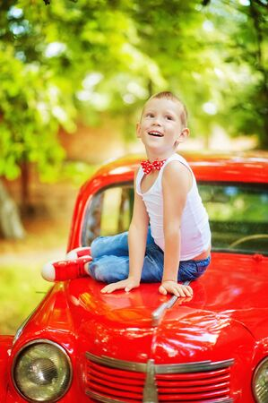5 years old boy in blue jeans, white t-shirt and red bow tie sit on red retromobile old car and look up. Happy child outdoor. Vintage style. 60-s lifestyle. Stylish boy in summer clothes. Reklamní fotografie