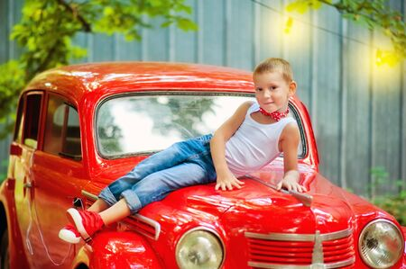 5 years old boy in blue jeans, white t-shirt and red bow tie lay on red retromobile old car and look up. Happy child outdoor. Vintage style. 60-s lifestyle. Stylish boy in summer clothes.
