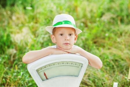 5 years old boy in summer hat sit on ground with his hands on white old fashioned scales. Summer time. Children play outside in summer. Serious child with weights outdoor. Close to nature childhood. Фото со стока