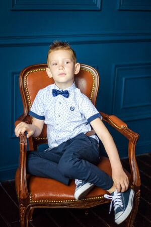 Portrait of 7 years old caucasian boy in blue bow tie and blue sneakers sitting in big brown leather chair. Fashionable good looking little boy sit on chair and look in camer Stock fotó
