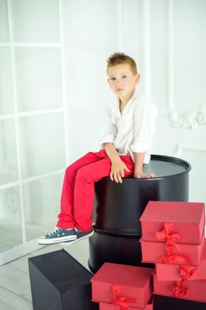 Portrait of 6 years old fashionable stylish boy in red pants and white shirt sitting on big black barrel. Red gift boxes around. Tank of gas like a present. Special Valentine day.