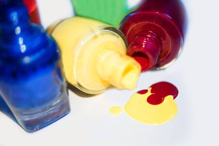 Close up of 5 open bottles of nail polish blue, red, green, yellow isolated on white background. Open yellow and red bottle lay down and splatter. Bright and colorful manicure and pedicure