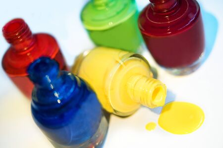 Close up of 5 open bottles of nail polish blue, red, dark red, green, yellow isolated on white background. Open yellow bottle lay down and splatter. Bright and colorful manicure and pedicure