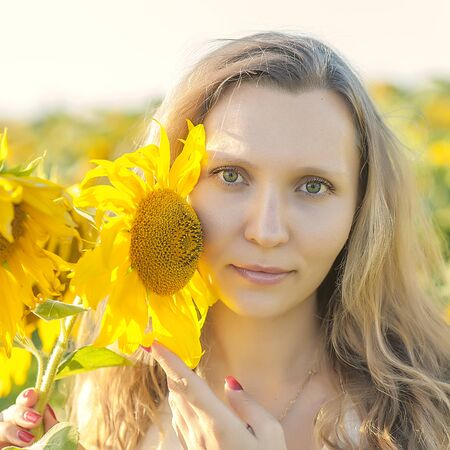 Young girl holding sunflowers outdoor shot. Portrait of beautiful blonde girl with bright yellow sunflower in hands on sunflowers field. Beautiful woman posing. Summer pollen allergy time