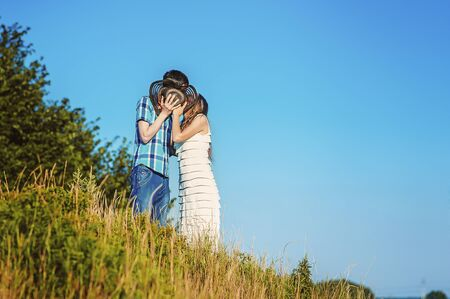 Happy married couple kiss each other behind hat on hill in summer. Blue sky and copy space for text. Faceless people in love together. Men and women kissing anonymous. Romantic in countryside. 版權商用圖片