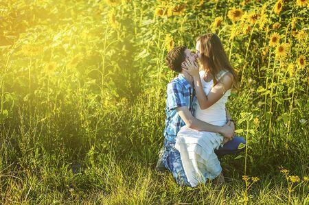 Giovane coppia uomo e donna fidanzata e fidanzato moglie e marito in piedi nel campo di girasoli che si baciano. Amore, romanticismo, solidarietà, fiducia. Felice matrimonio. Girasole in estate.
