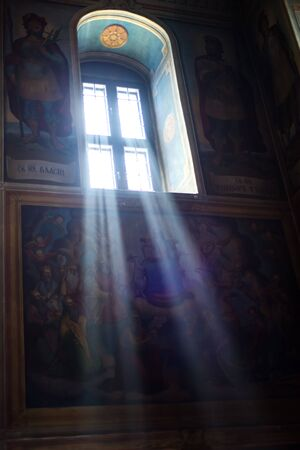 Vertical picture of rays of light from arch window in dark orthodoxal church with blue walls and painting on them. Sunny day in old dark cathedral.