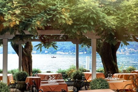 Beautiful scenic view on cozy restaurant in Bellagio on Lake Como, lombardy, North Italy with water of Como, small boat and Alps mountains on background. Famous tourist destination. Travel.
