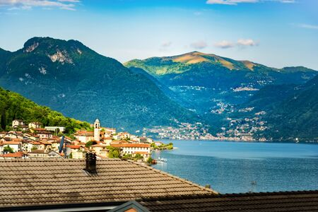 Amazing view of Como Lake from Lezzeno, panorama of lake with rooftops in front of it and green sunny Alps mountains on background. Vacation on Como, Lombardy, Italy. Popular tourist destination.