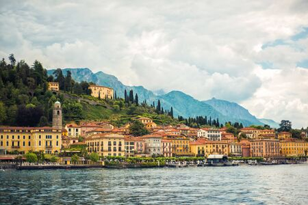 Amazing view of Como Lake and Bellagio, panorama of lake with small town and Alps mountains on background in cloudy day. Vacation on Como, Lombardy, Italy. Popular tourist destination. Italian city Archivio Fotografico