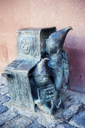 Two dwarfs repairing atm in Wroclaw, Poland. One of famous sculptures of dwarfs in Wroclaw, Breslau in past, symbols of polish city. Travel destination. Tourism attraction.