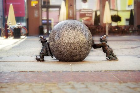 Two dwarfs pushing granite ball in Wroclaw, Poland. One of famous sculptures of dwarfs in Wroclaw, Breslau in past, symbols of polish city. travel destination. Tourism attraction. Banco de Imagens
