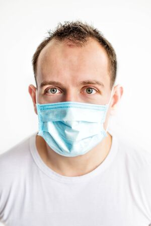 Vertical close-up portrait of scared caucasian man in blue medical mask on face, afraid of coronavirus. Health care in cold season. Scared expression.