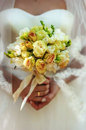 Beautiful wedding bouquet with creamy and yellow roses in brides hands in wedding day. Wedding decor. Idea for bridal bouquet. Flowers in womans hands.