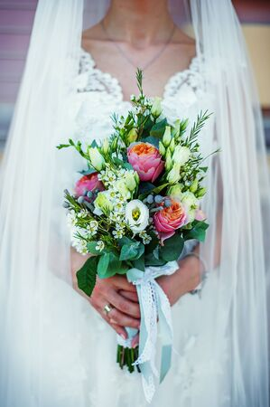 Beautiful wedding bouquet with pink and white roses in brides hands in wedding day. Wedding decor. Idea for bridal bouquet. Flowers in womans hands. Reklamní fotografie
