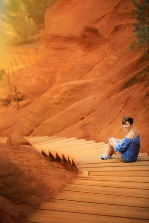 Vertical picture with young woman tourist on vacation sitting on path in ochre quarry in one of the most beautiful village of France Roussillon in Provence. Famous travel tourism destination. Stock Photo