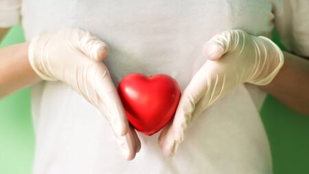 Close-up of hands in medical gloves holding red heart. Concept for charity, health insurance, love, international cardiology day, hope, donation and help during coronavirus covid-2019 pandemic. 写真素材