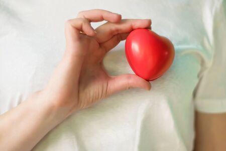 Close-up of hand holding red heart. Concept for charity, health insurance, love, international cardiology day, hope, donation and help during coronavirus covid-2019 pandemic.