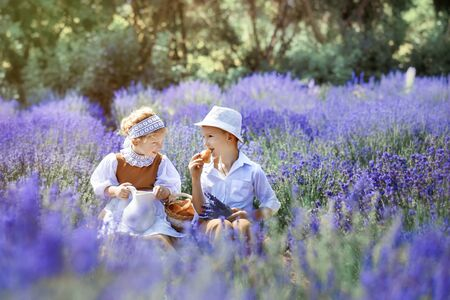 Village scene with children in vintage clothes in middle of lavender field. Girl in brown dress with white apron and boy in white hat, shirt and brown trousers have picnic on lavender. Eating outdoor.