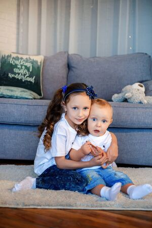 Cute little caucasian kids siblings hug and cuddle at home show love and care, small girl sister embrace toddler brother, take care of cousin, family relationships, children support concept