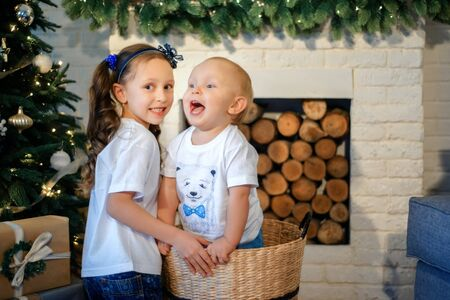 Cute little caucasian kids siblings laughing at home show love and care, small girl sister embrace toddler brother, take care of cousin, family relationships, children support concept