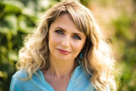 Close-up portrait of beautiful smiling blonde 40 years old woman in blue shirt looking in camera outdoors in back light. Healthy lifestyle and shining skin in age of 40s