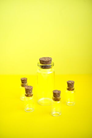 Vertical picture of multiple mini transparent glass bottles with closed brown cork lids on yellow background. Rustic and vintage jars small and clean. Old medicin keepings.