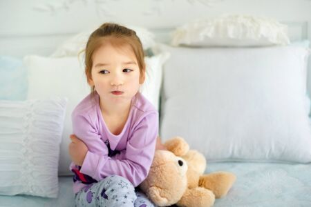Portrait of small 3 years old sulking capricious girl sitting in bed in pajama with her toy bear. Emotional child. Kid in bad mood. Sad little girl in nightwear.