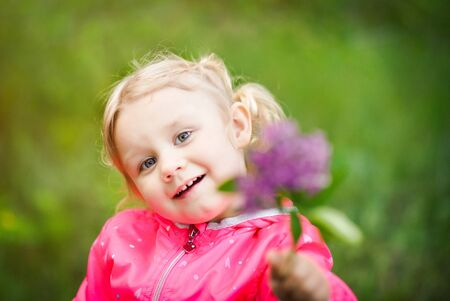 Portrait of little 3 years old blonde girl in pink jacket with branch of purple lilac in hand. Defocused lilac and smiling kids face. Blossom spring concept.